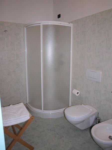 un bagno con un box doccia e un tavolino con degli asciugamani