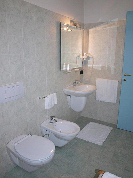 un bagno con wc, bidet e un lavabo di color bianco