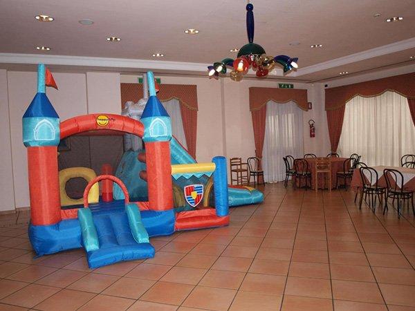 Dei tavoli rotondi e sulla destra l'area giochi per bambini