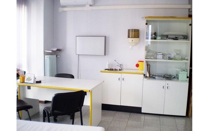 una scrivania bianca e sul retro dei mobili bianchi
