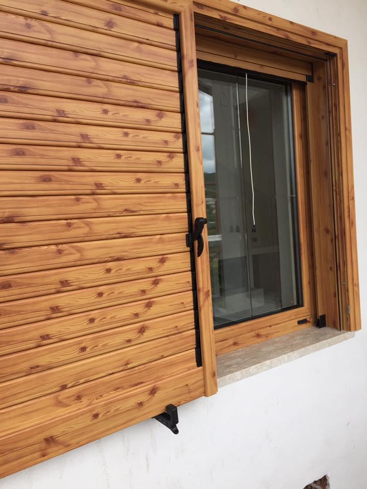 una finestra chiusa con l'anta in legno di una persiana aperta