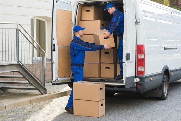 Due ragazzi che scaricano degli scatoloni da un furgone