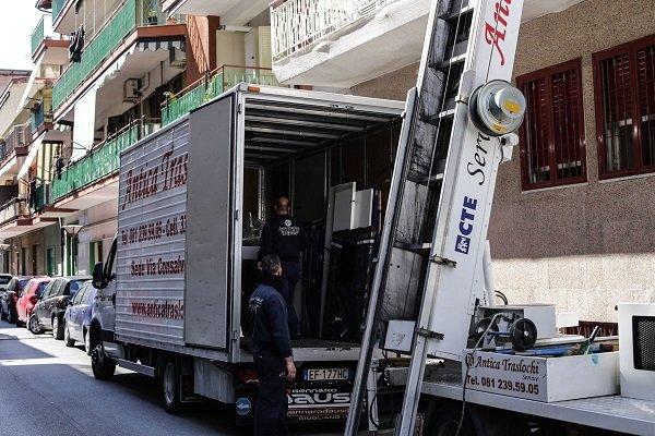 Due uomini dentro un rimorchio di un camion dei traslochi e una scala aerea