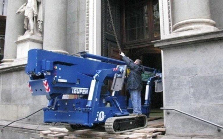 un operaio assicura l`ancoraggio di una catena ad una macchina per l`edilizia