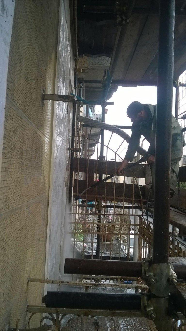 operaio durante un processo di sabbiatura di una facciata