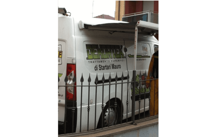 furgone della ditta DEKORTEK parcheggiato vicino a una ringhiera di ferro