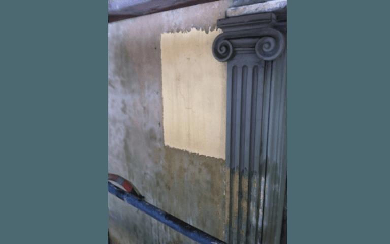 muro con decorata una colonna greca danneggiato