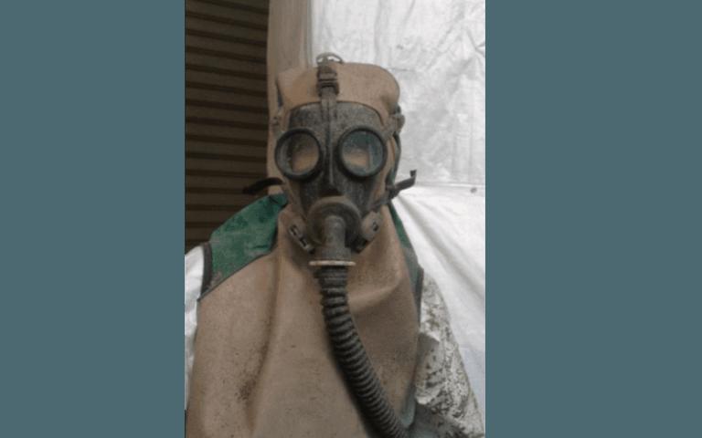 addetto con tuta protettiva e maschera integrale