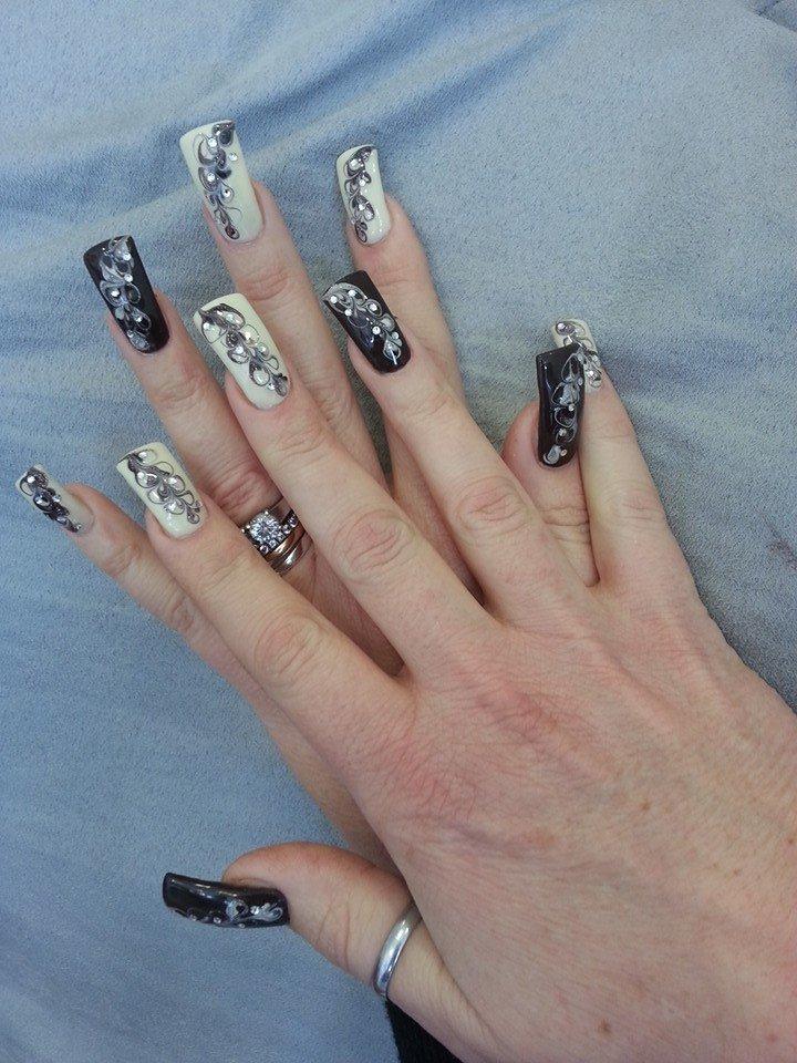 unghie bianche e nere con brillantini e disegni