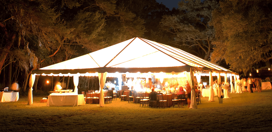 large marquee with open sides, lit from within, at night