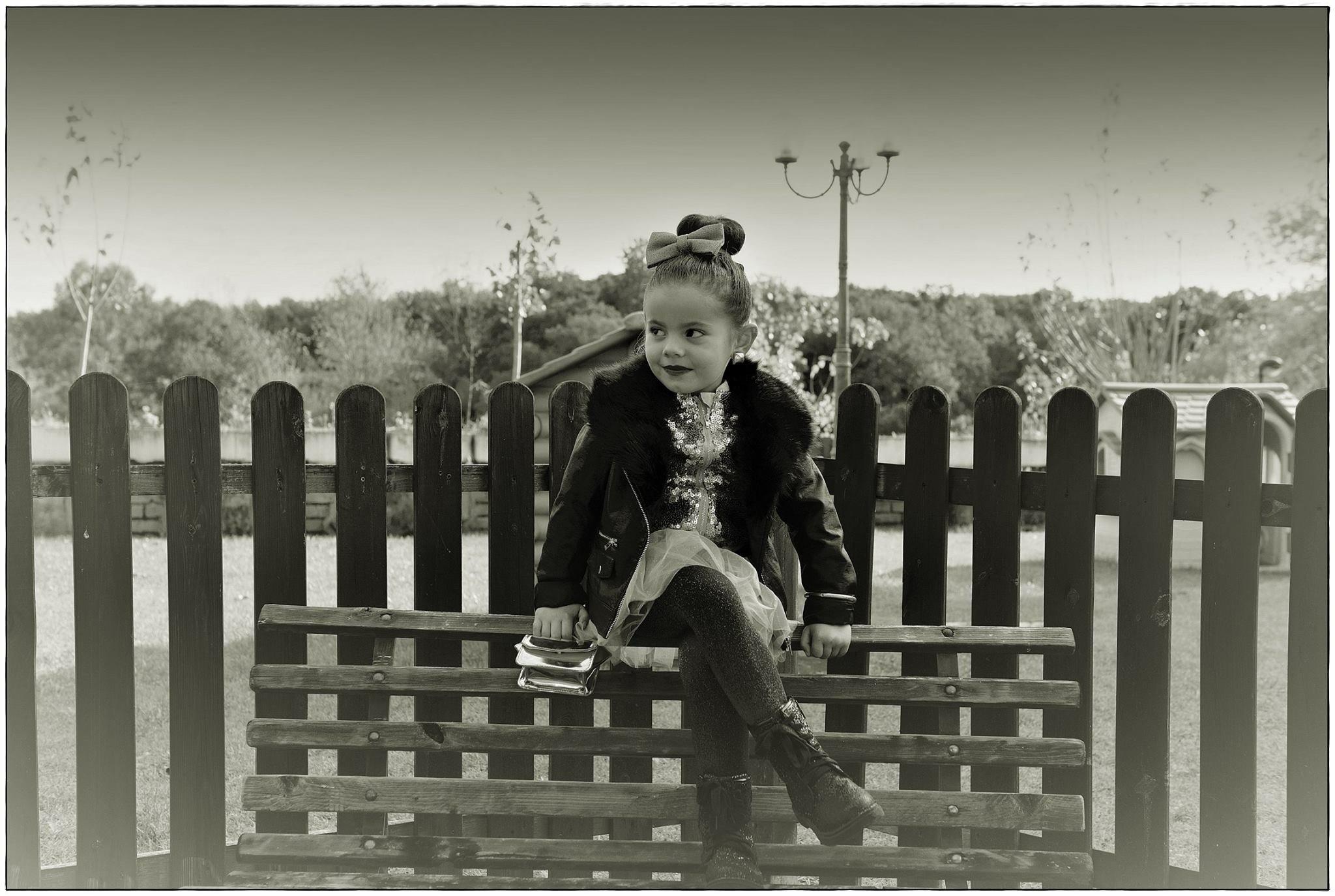 Bambina seduta su staccionata