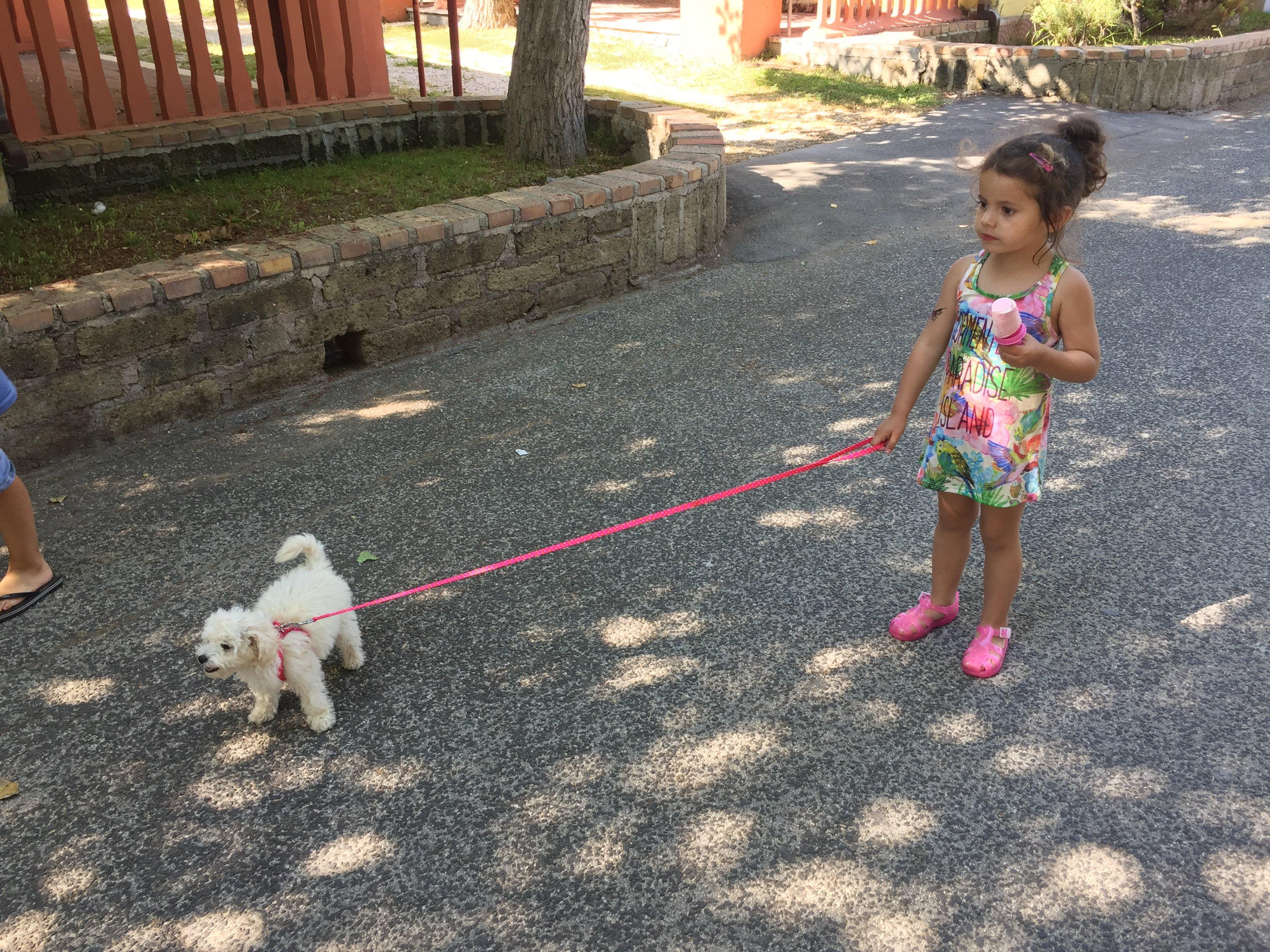 Bambina con cagnolino al guinzaglio