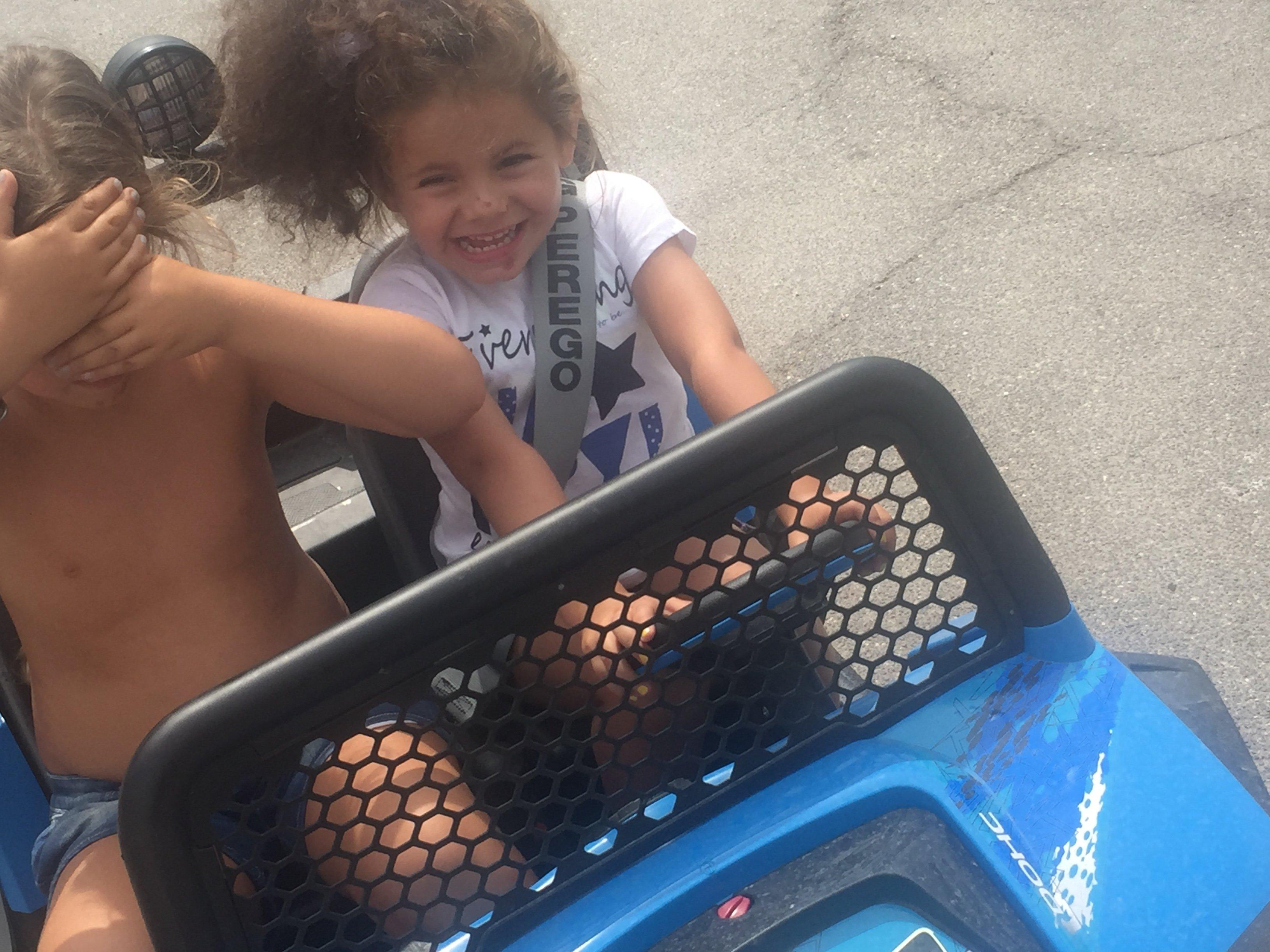 Due bambini che giocano su una macchinina elettrica