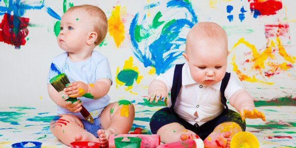 Due bebè su sfondo di parete pitturata