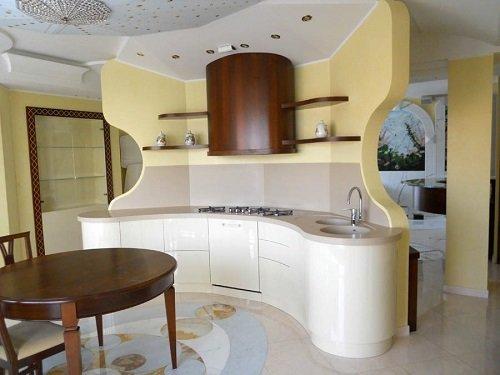 una cucina moderna curva di color beige e accanto un tavolo in legno
