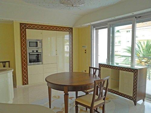 dei mobili da cucina di color avorio e un tavolo rotondo in legno