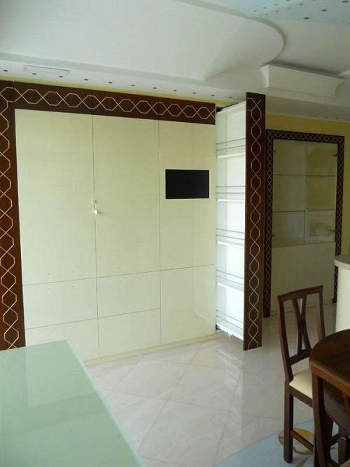 un mobile da cucina in legno di color avorio con bordi di color marrone