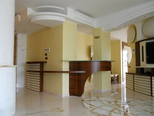 una sala con un bancone in legno a curva e un pavimento in marmo