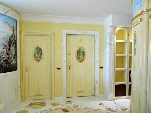 due porte in legno di color avorio con sopra un disegno ovale