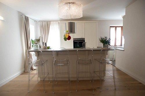 una cucina con una penisola in legno di color bianco e delle sedie in plexiglass