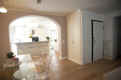 una cucina con mobili di color avorio e delle sedie in plexiglass