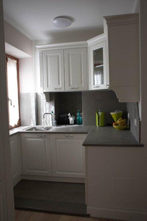 una cucina ad angolo di color bianco e un top di color grigio