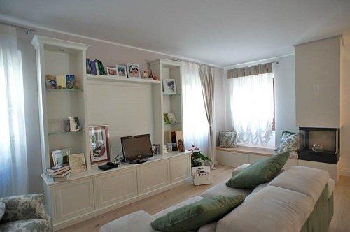 una sala con un mobile da tv in legno di color bianco e un divano di color bianco e verde