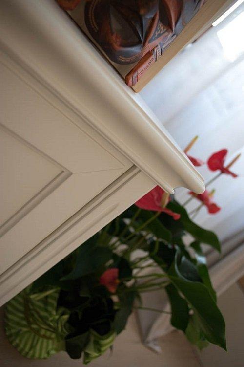 un mobile in legno di color bianco e accanto un vaso di fiori