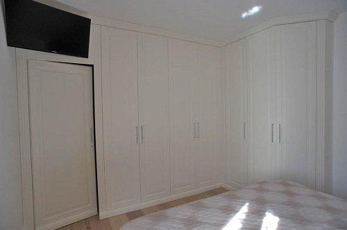 una camera con gli armadi a muro di color bianco e una Tv