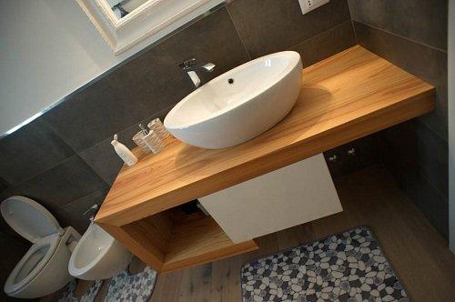 un bagno con una mensola di legno con sopra un lavabo a forma ovale