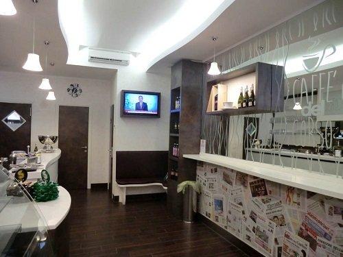 interno di un un bar con dei banconi di color bianco e delle vetrate