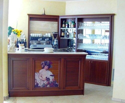 un mobile da bar in legno con una macchina del caffè e delle mensole con dei bicchieri sopra