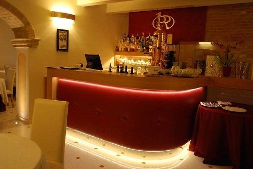 un bar con un bancone a curva di color rosso e bianco e delle luci accese