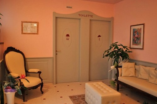 una sala d'attesa con un divano e una poltrona accanto ai bagni