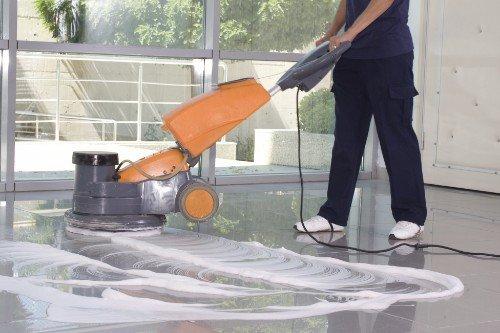 addetto alle pulizie pulisce pavimenti con macchinario professionale