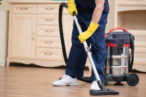 addetto alle pulizie passa l'aspirapolvere