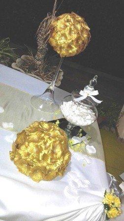 un tavolo con un vaso con dei confetti e decorazioni dorate