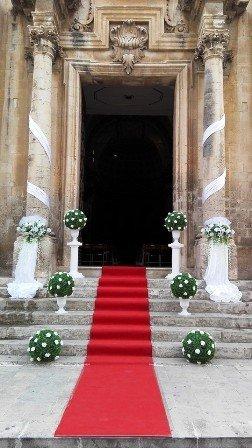 tappeto rosso davanti a una chiesa e dei bouquet di fiori ai lati