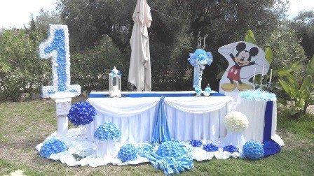 un tavolo con una tovaglia bianca dei fiori blu e un cartello di Topolino