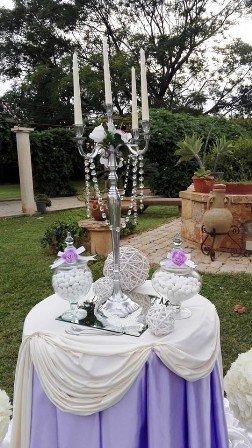 un tavolo con una tovaglia bianca e lilla e un candelabro