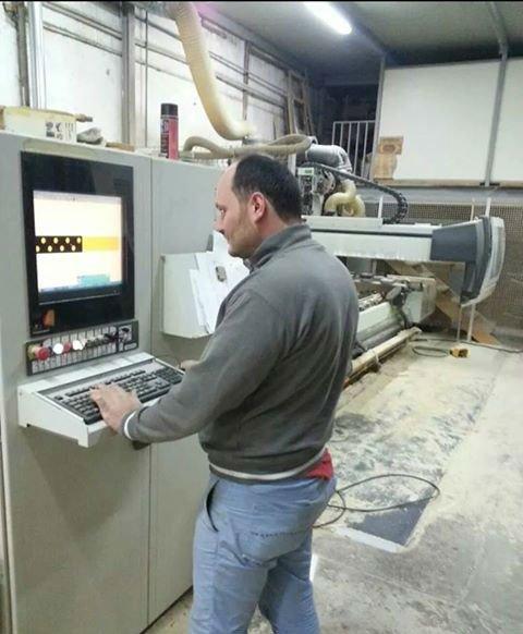 un uomo che lavora ad un macchinario all'interno della falegnameria