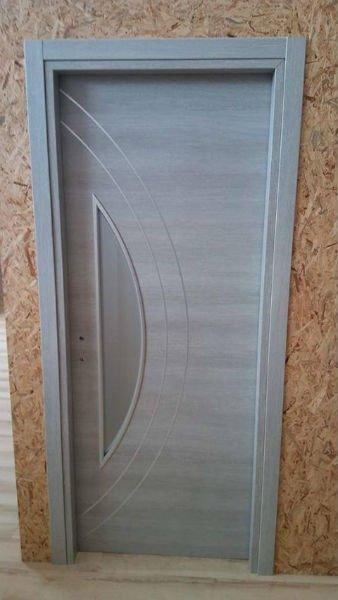 una porta grigia con un vetro sul lato sinistro