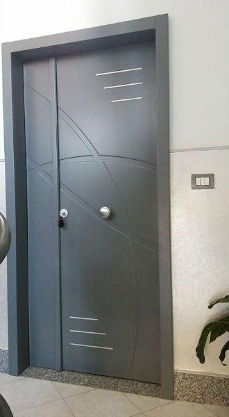 una porta blindata grigia con un pomello in acciaio