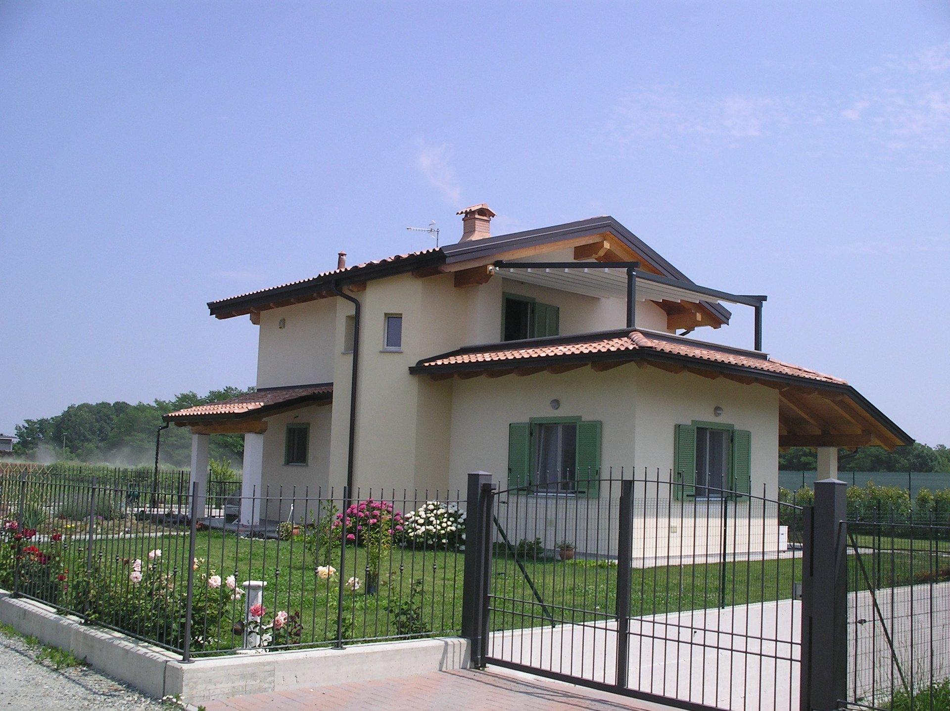 una casa indipendente con giardino verde , cancello in ferro e ringhiera