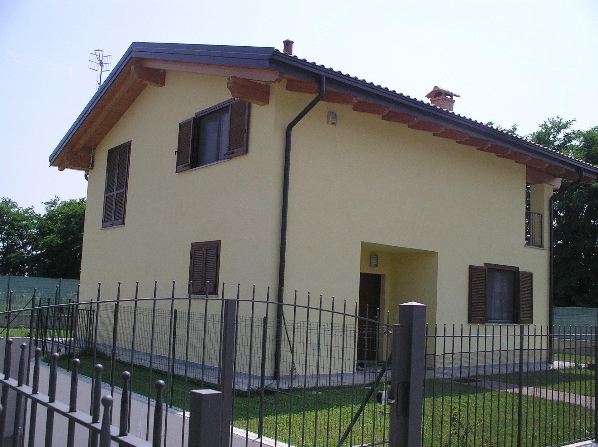 vista esterna di una casa indipendente con persiane, prato verde e cancelli in ferro