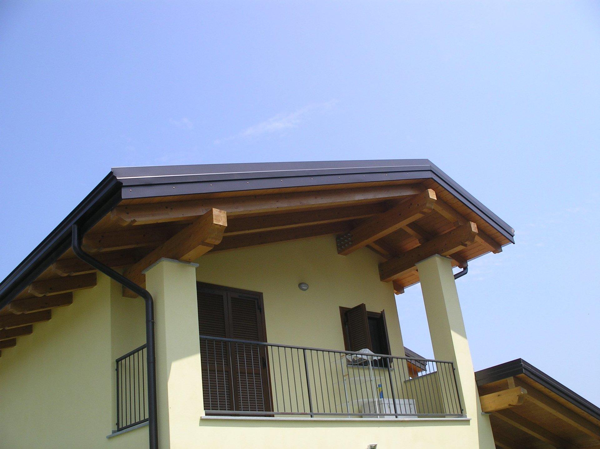 una casa gialla con tettoia in legno