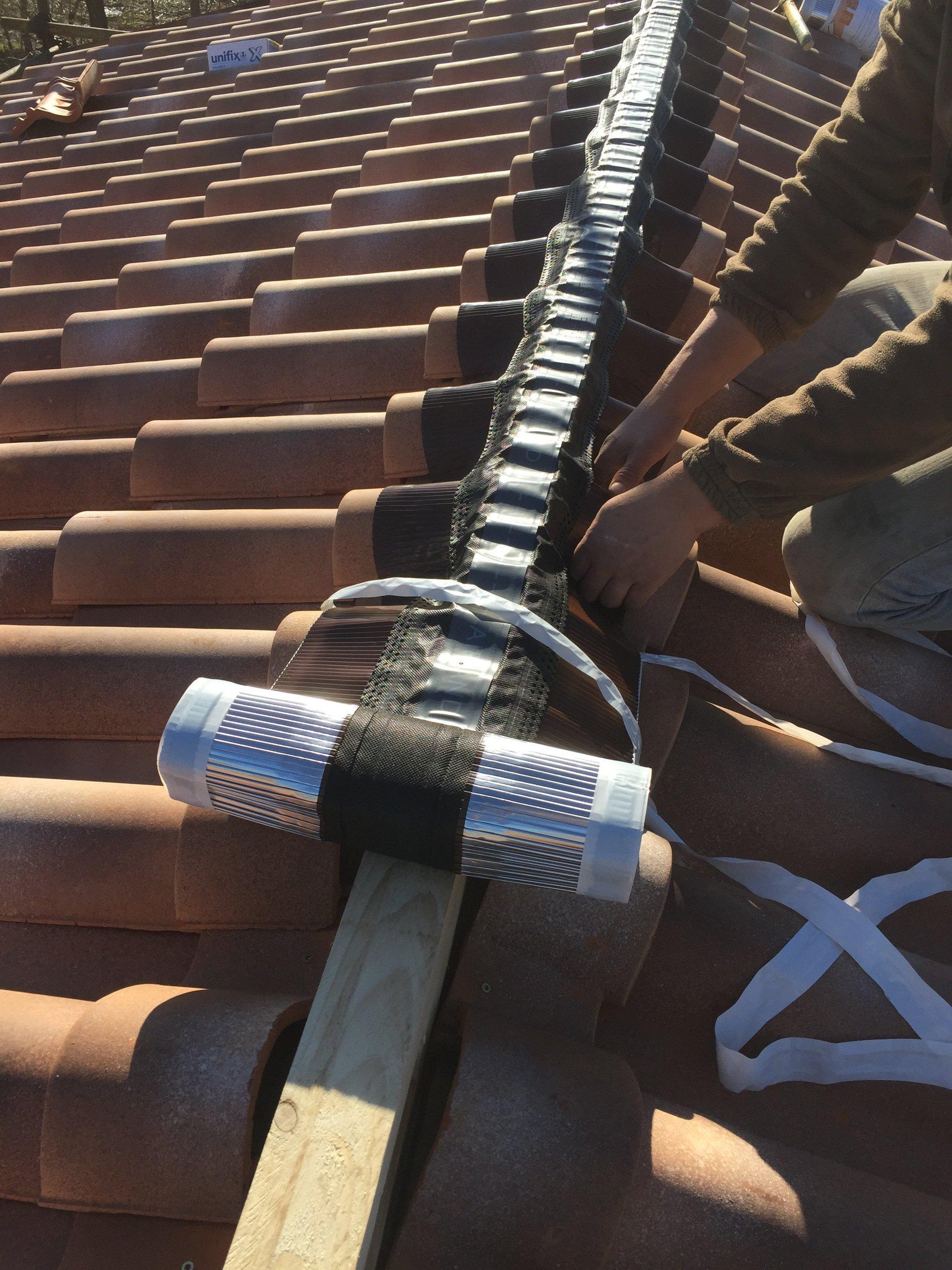 operaio mentre assicura delle linee vita sul tetto