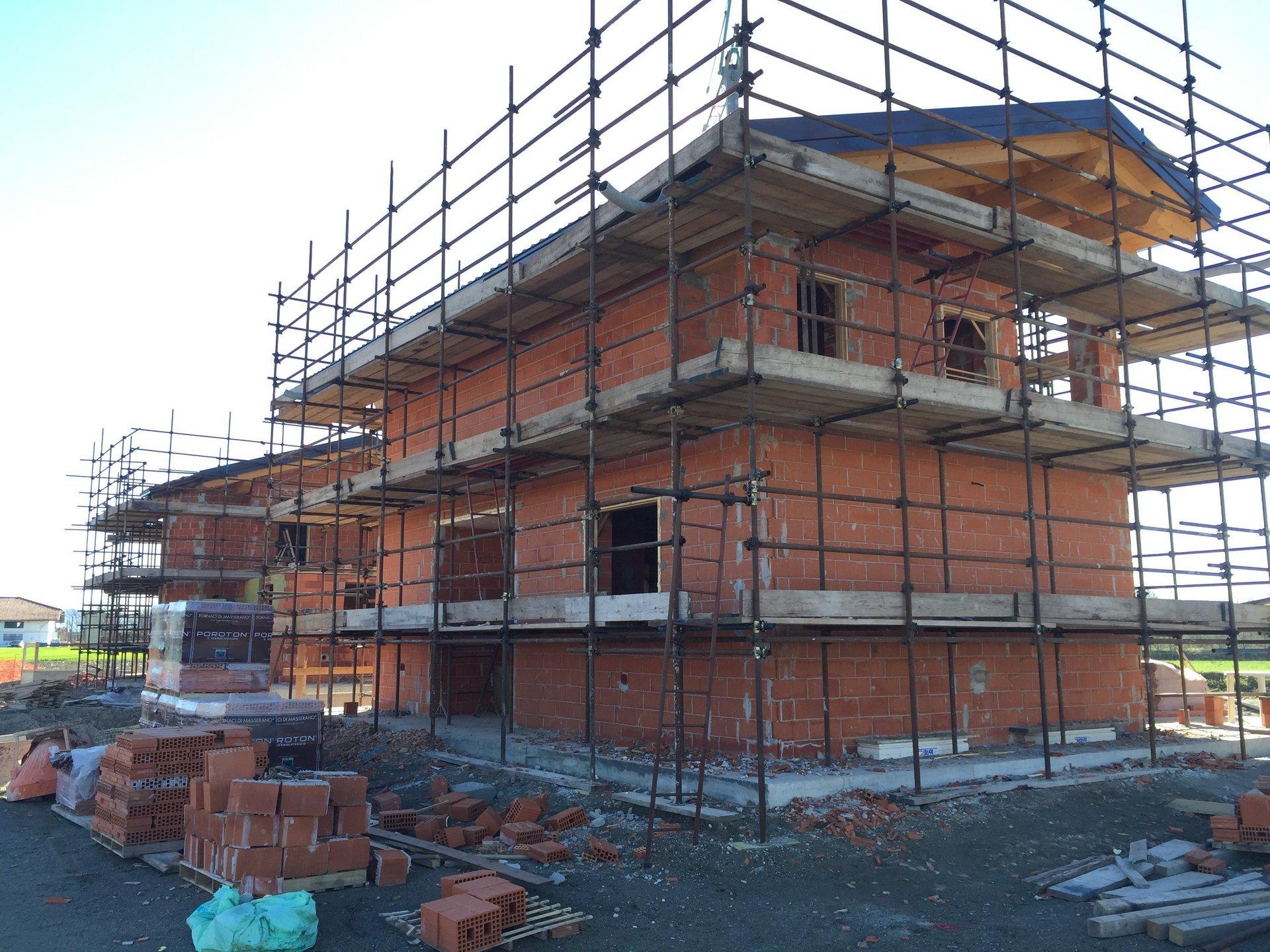 vista angolare di una casa durante ristrutturazione con ponteggi