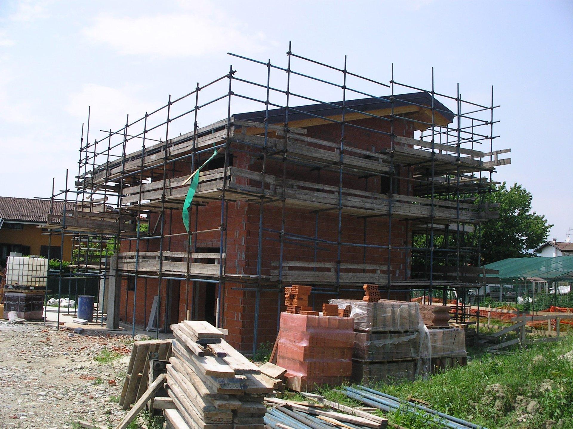 vista frontale di una casa durante ristrutturazione con ponteggi e materiali edili