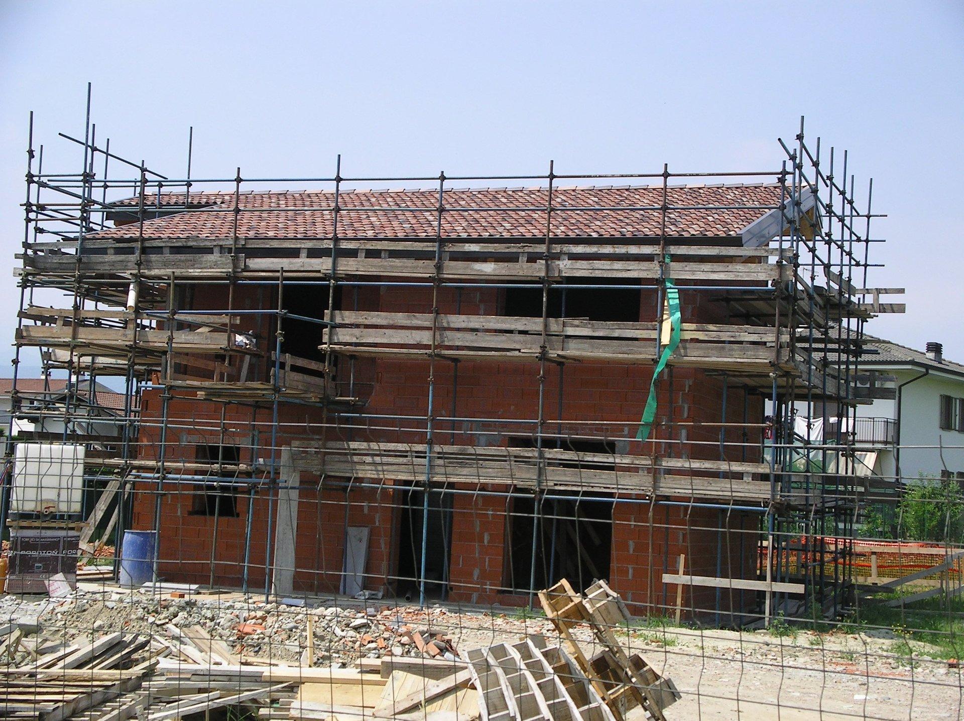 una casa durante ristrutturazione con ponteggi e materiali edili